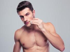 Mann, der Gesichtshaut mit Wattepads reinigt foto