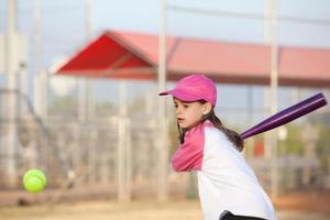 kleines Mädchen schwingt am Baseball foto