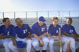 Baseballmannschaft auf Bank im Stand während des Baseballspiels (von hinten beleuchtet)