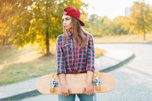 schöne und modische junge Frau, die mit einem Skateboard aufwirft foto