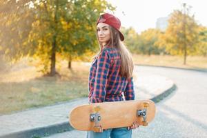 schöne und modische junge Frau, die mit einem Skateboard aufwirft