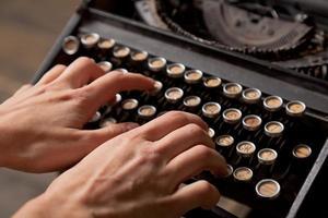 menschliche Handabdrücke auf Retro-Schreibmaschine.