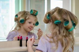 blondes Mädchen mit Lippenstift und Lockenwicklern