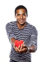 dunkelhäutiger junger Mann, der ein Objekt in Herzform hält foto