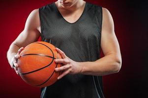 junger männlicher Basketballspieler, der den Ball greift foto