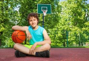 Junge sitzt allein mit Ellbogen auf dem Ball foto