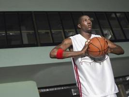 Basketballspieler, der sich darauf vorbereitet, den Ball weiterzugeben foto
