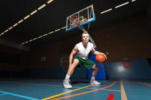 harter gesunder junger Mann, der Basketball in der Turnhalle spielt. foto