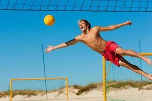 Mann am Strand springt in die Luft, als er versucht, Volleyball zu bekommen foto