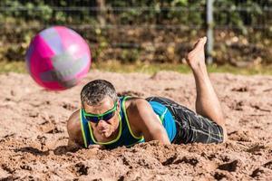 Beachvolleyballer im Sand liegen foto