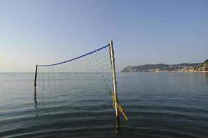alassio. Beachvolleyballnetz in ruhigem Wasser.