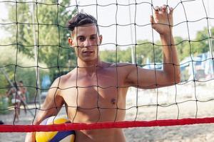 Porträt des Volleyballspielers, der vor Netz steht foto
