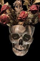 menschlicher Schädel mit getrockneten Rosen