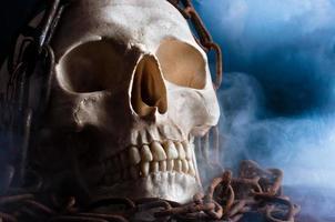 menschlicher Schädel mit Kette und Rauch foto