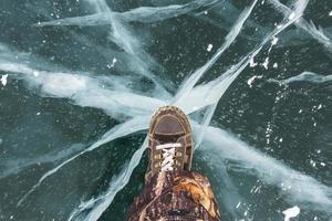 menschliche Füße in Stiefeln auf dem Eis