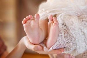 Babyfüße in Mutterhänden. Mutter und ihr Kind.