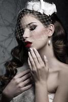 elegante Dame im Pelzmantel mit Schleier- und Nageldesign
