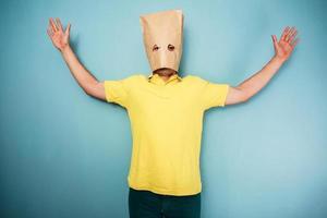 junger Mann mit Tasche über Kopf und erhobenen Armen foto