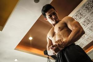 Bodybuilder schaut seinen Muskel