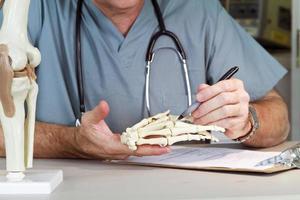 Arzt, der ein Handgelenk studiert foto