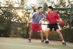 zwei Straßenspieler auf dem Basketballplatz foto