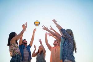 glückliche Freunde, die Volleyball werfen foto
