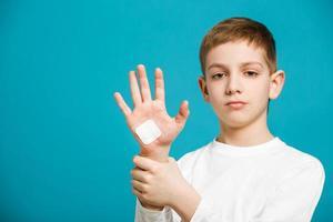 trauriger Junge mit weißem Heftpflaster auf seiner Hand foto