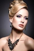 schönes Mädchen mit hellem Make-up und Abendfrisur. foto