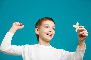glücklicher Junge mit Gipskreuz in der Hand foto