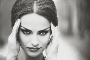 Hübsches brünettes Mädchen berührt ihren Kopf wegen Kopfschmerzen foto