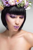 schöne brünette Frau mit Blumen auf dem Kopf foto