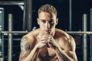 Nahaufnahmeporträt eines muskulösen Manntrainings mit Langhantel an