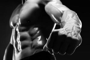 Der hübsche muskulöse Bodybuilder zeigt seine Faust und Vene. foto
