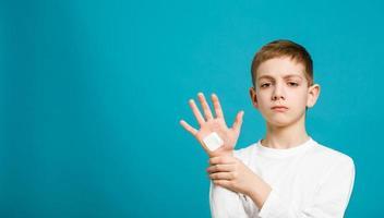 unglücklicher Junge mit weißem Heftpflaster auf seiner Hand foto