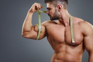 Bodybuilder, der Bizeps mit Maßband misst