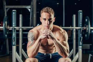 Nahaufnahmeporträt eines muskulösen Manntrainings mit Langhantel an foto
