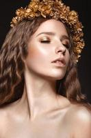schönes Mädchen mit goldenem Make-up und Herbstkranz foto