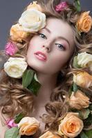 schönes Mädchen mit sanftem rosa Make-up und vielen Blumen foto