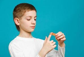 Junge klopft auf Heftpflaster an seiner Hand foto