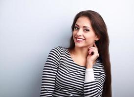 glücklich lächelnde junge lässige Frau mit langen Haaren suchen foto