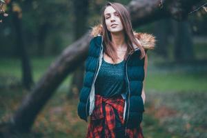 junges hübsches Mädchen, das nahe dem Baum steht.