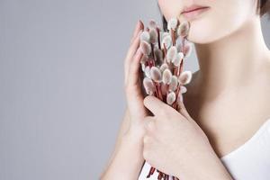 Frau mit Weidenzweigen in den Händen auf einem grauen Hintergrund foto