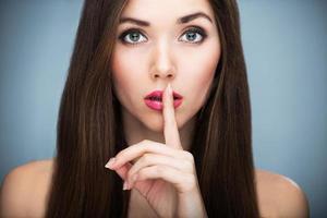 Frau mit braunen Haaren mit Fingern auf den Lippen foto