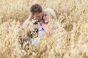 romantisches junges Paar, das inmitten des Feldes entspannt foto