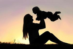 Silhouette der lachenden Mutter und des Babys, die draußen spielen foto