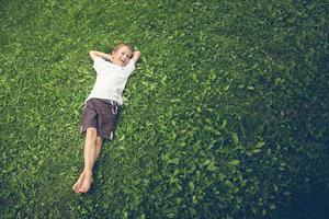 kleiner Junge, der im Gras liegt und lacht