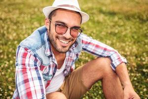 sitzender junger lässiger Mann, der für die Kamera lacht