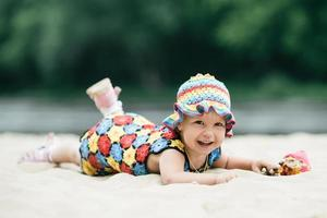 kleines Mädchen mit hellem buntem Kleid foto