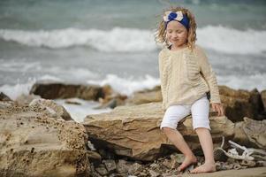 niedliches lockiges Kindermädchen, das am Strand spielt foto