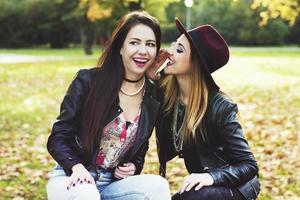 zwei Mädchen in einem Park auf einer Bank lachen